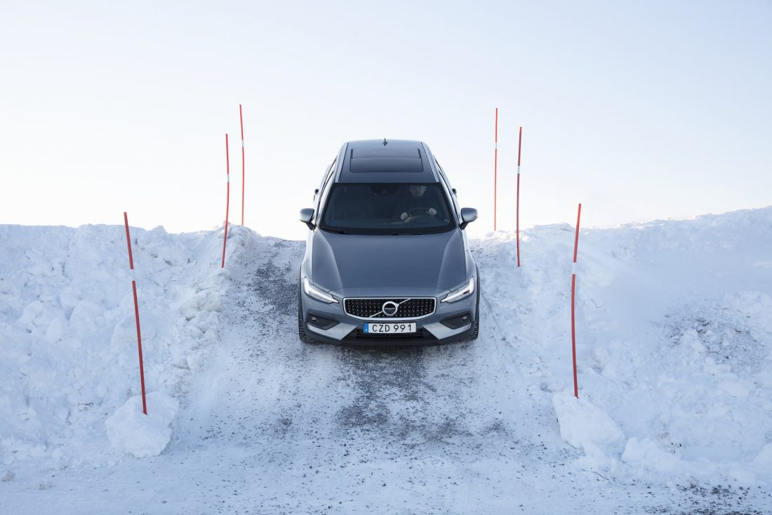Volvo V60 CROSS COUNTRY fährt einen Schnee bedeckten Abhang hinunter
