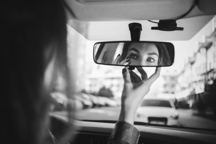 the girl behind the wheel looks in the rear-view mirror in the car and makes herself a make-up in black and white