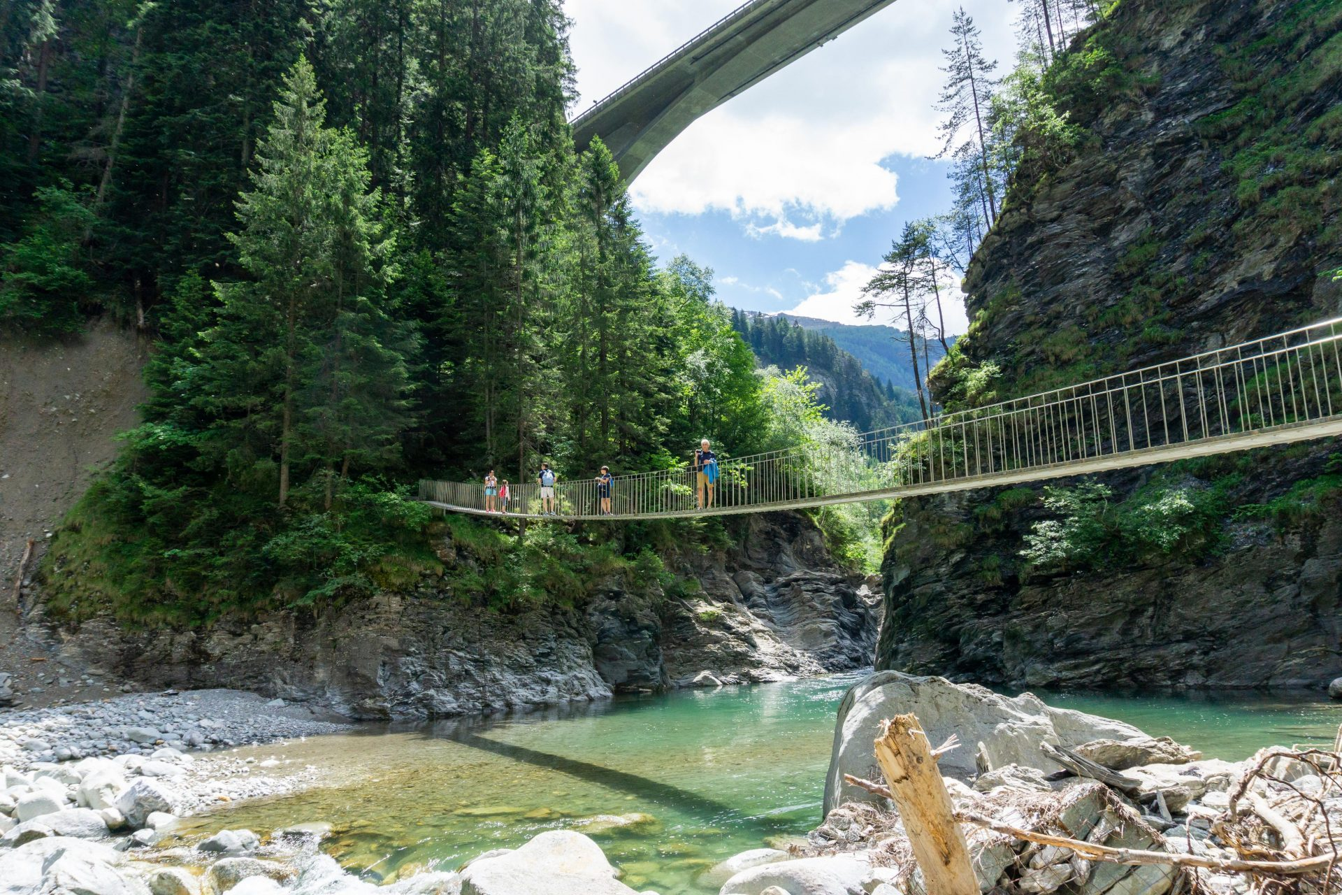 Family hiking across a wooden suspension bridge over the Rhine River in the Viamala Gorge in the Swis Alps