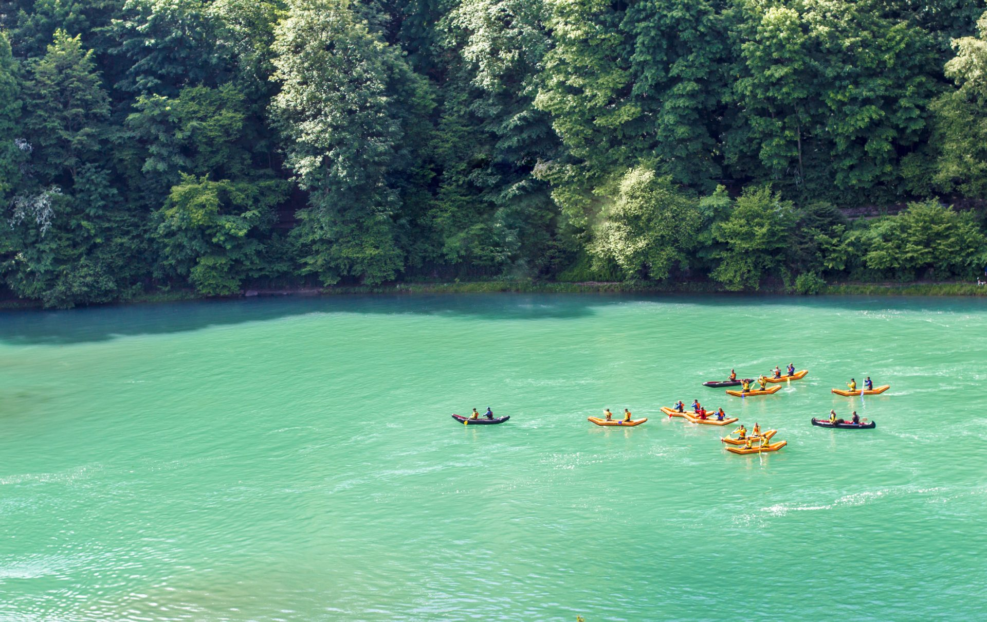 Kayaks on the river Aare. Rafting on the river Aare. Swimmers in Bern