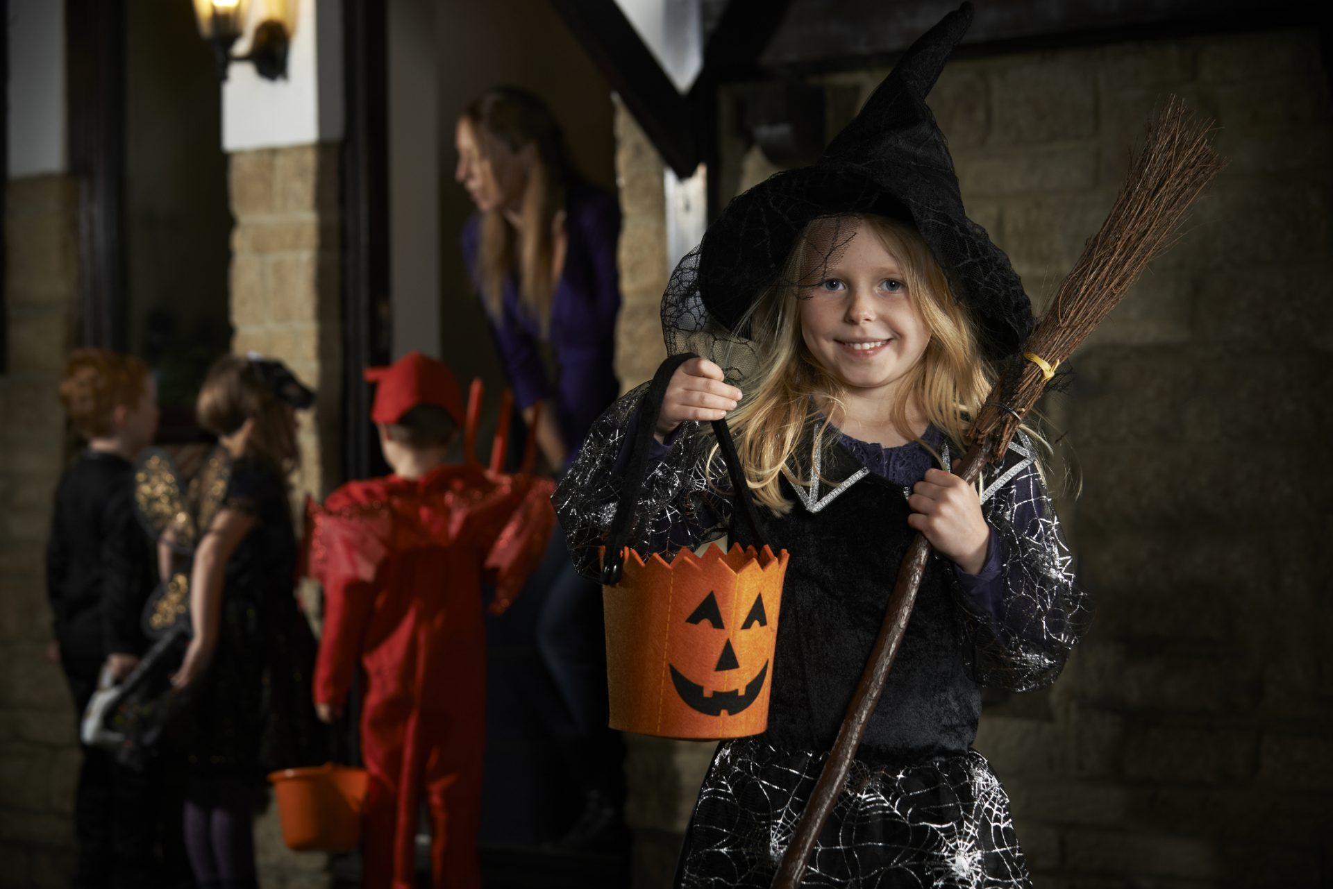 Young girl in a witch costume with tricker treaters behind