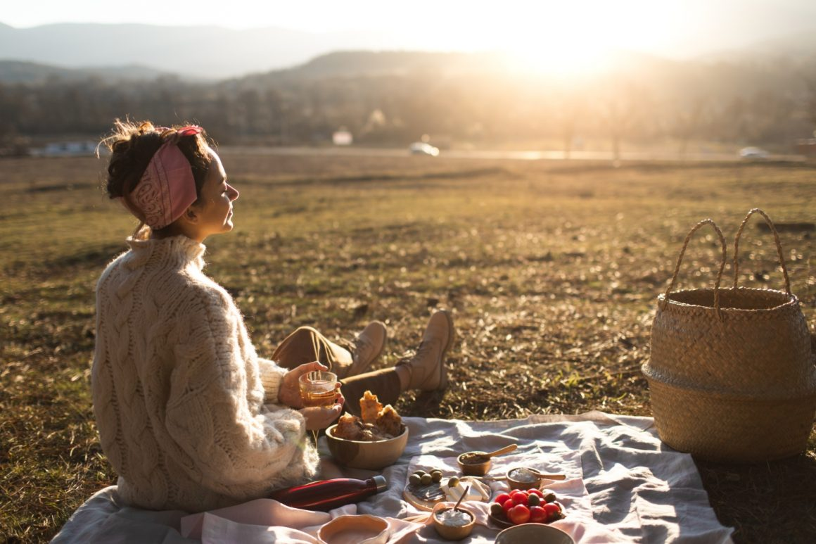 Back view of young woman relaxing and enjoying sunset in autumn. Happy beautiful girl on the nature picnic – camping. Cozy autumn outdoor concept.