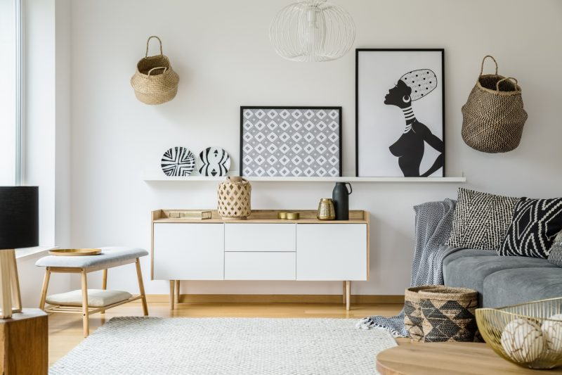 Posters and plates above wooden cupboard in boho living room interior with grey sofa. Real photo