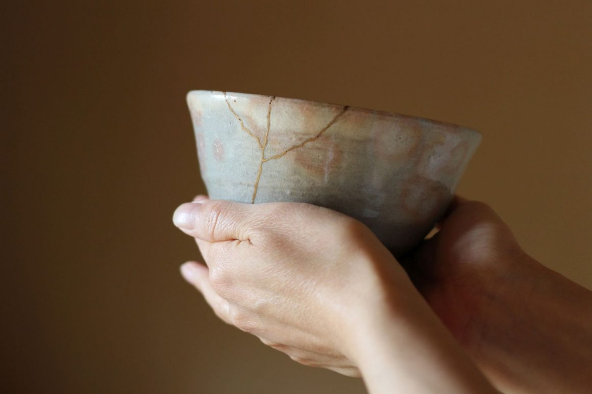 Repair of crack pottery tea cup with a hand