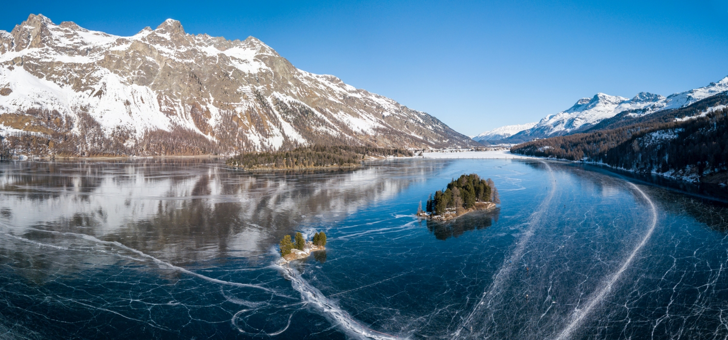 Aerial panorama image of the Chaviolas islets on the frozen lake of Silsersee in St. Moritz, Switzerland