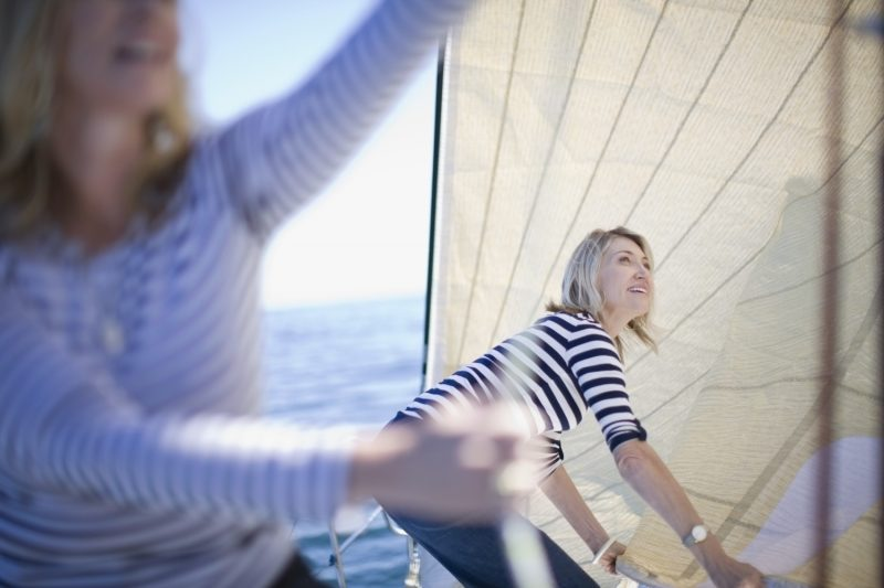 Women adjusting sails on boat