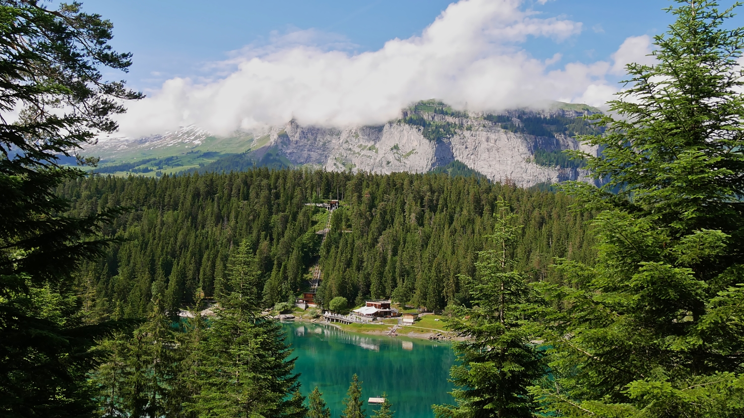 Turquoise colored lake Caumasee surrounded by forest reflected in the water near Flims, Grisons, Switzerland with funicular, restaurant and mountains in background.